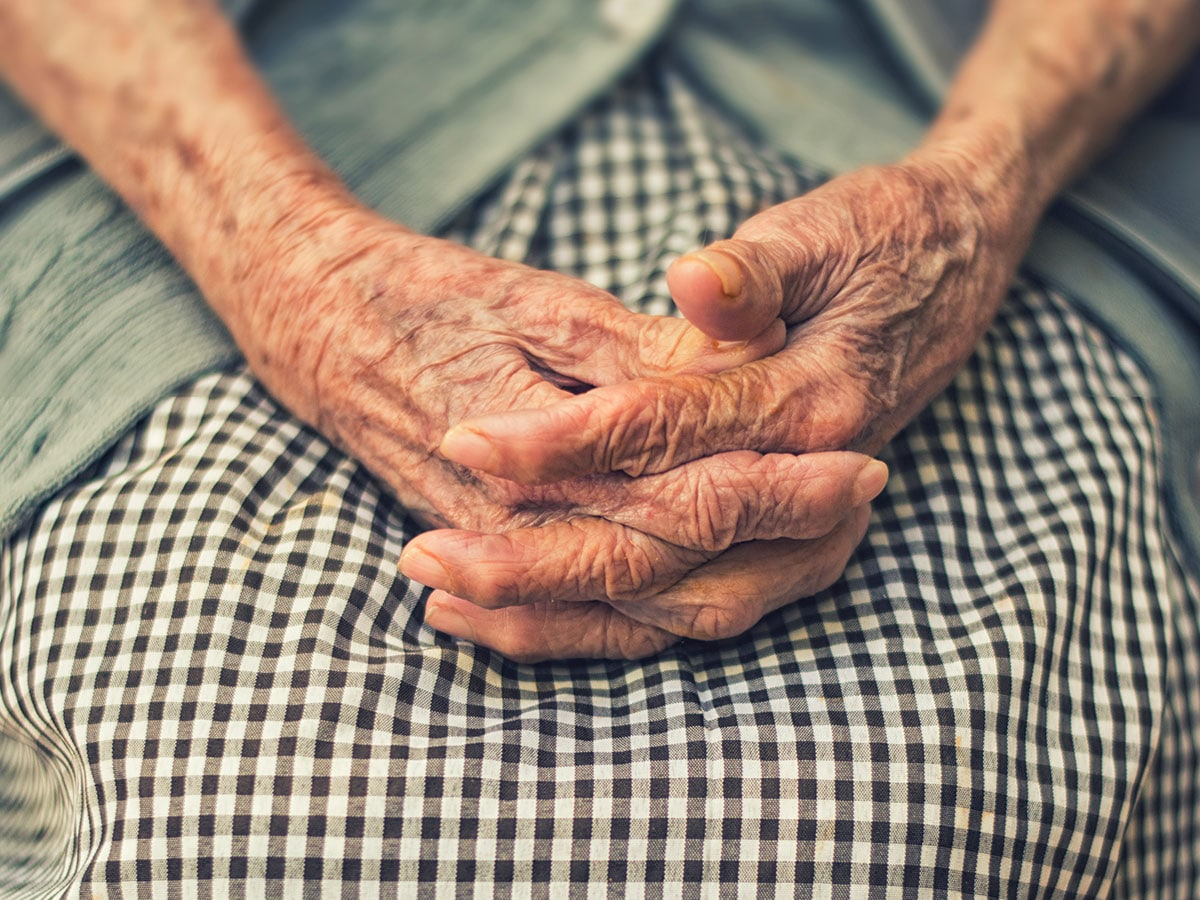 aging woman sitting with hands crossed
