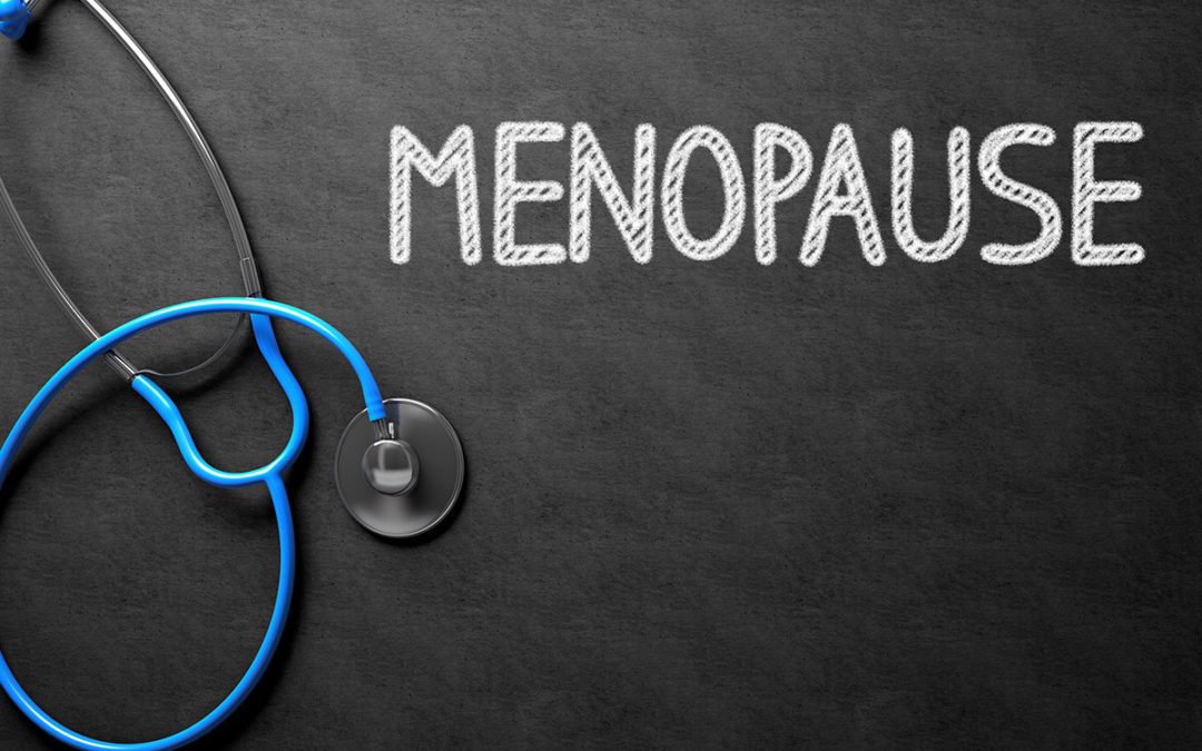 Word Menopause written on a chalkboard next to a stethoscope