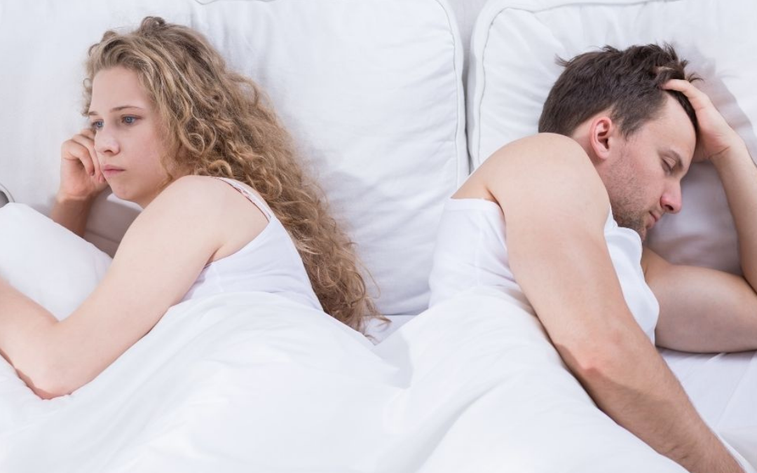 Possible couple candidate for a sleep divorce lay in bed with their backs to each other while the man sleeps and his female partner lays wide awake looking unhappy.